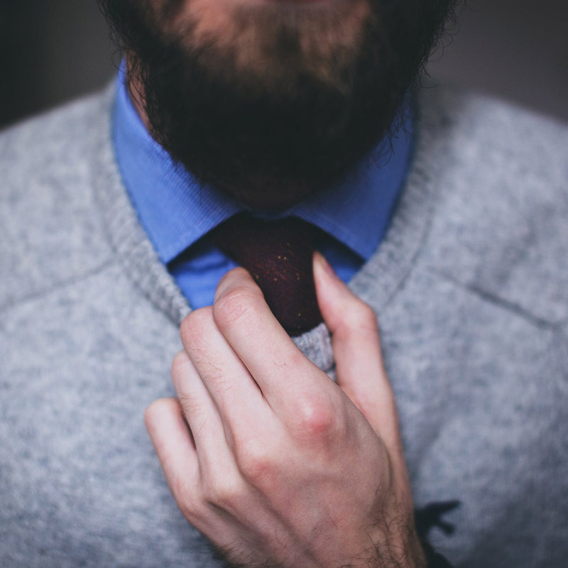 Man with beard in a grey sweater and blue button-up shirt adjusting his red tir